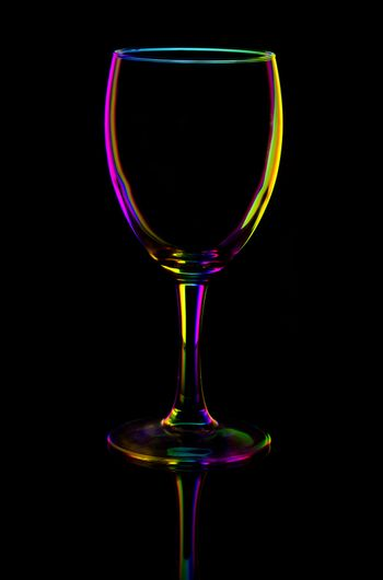 transparent colored empty wine glass, isolated on black