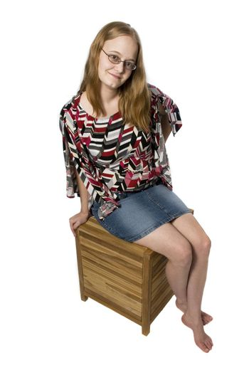 young woman posing on a wooden box bench