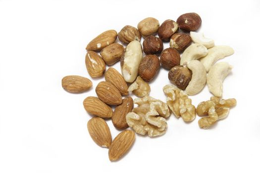 mixed nuts of almonds,brazil,casher,hazelnuts,and walnuts over a white background