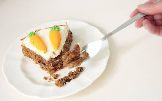 using a fork to eat a slice of carrot cake