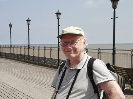 mature smiling man out for a daytrip standing on the pier