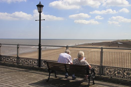 elderly couple sitting on a bench looking across at the beach