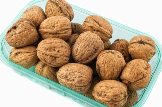 Walnuts in plastic container isolated on white