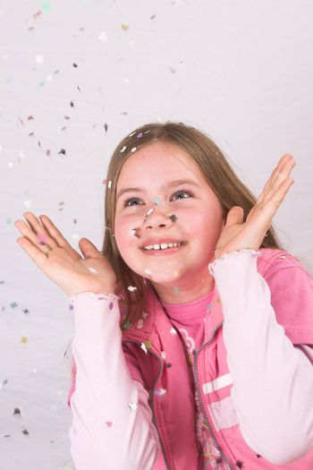 Cute blond girl throwing confetti in the air and watching it come down