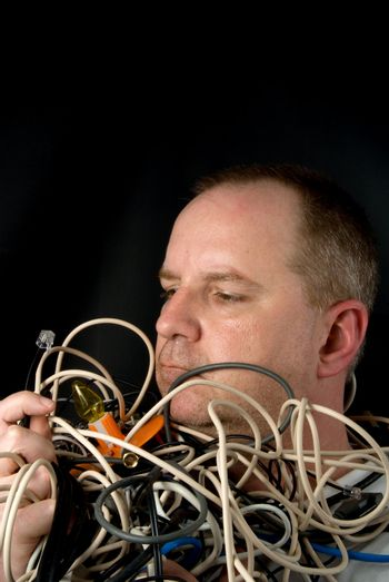 A man tangled up in wires and cables.