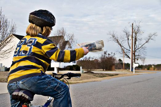 a boy delivering newspapers