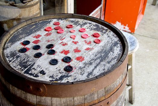 Checkers on a board made from an old barrel.