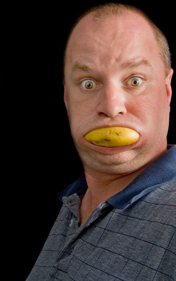 A man with a fresh banana stuck in his mouth.