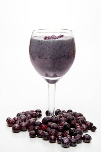 A Blueberry Smoothie surrounded by frozen blueberries.