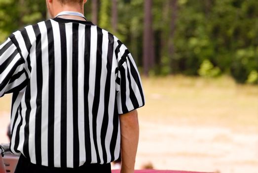 A sports referee wearing a traditional officials shirt.