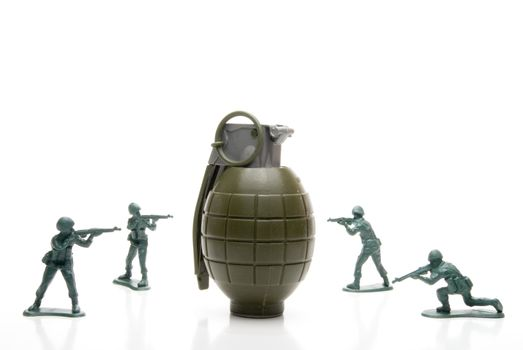 Several toy soldiers surrounding a hand grenade.