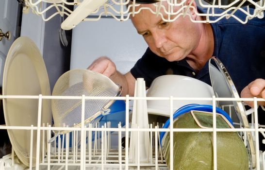 A man loading or unloading a dishwasher.