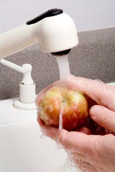 A person vigorously washing a delicious apple.