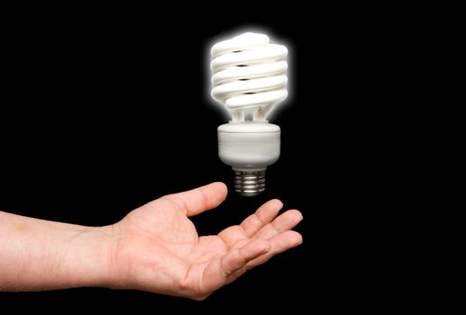 A florescent light bulb floating above a hand.