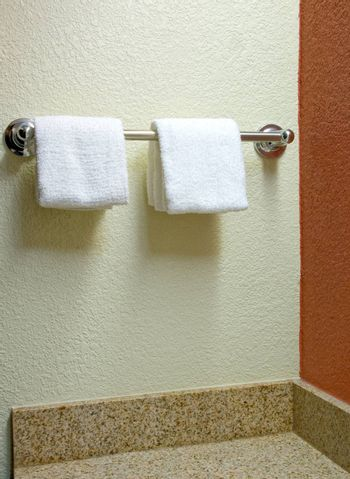Towels hanging on a rack in a bathroom.
