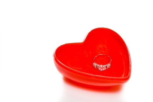 A diamond wedding ring on top of a red heart.