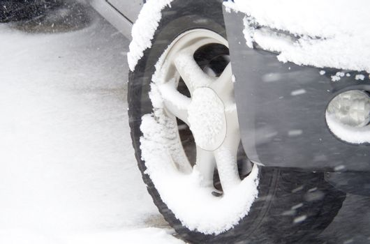 Snow on a truck tire as snow falls.