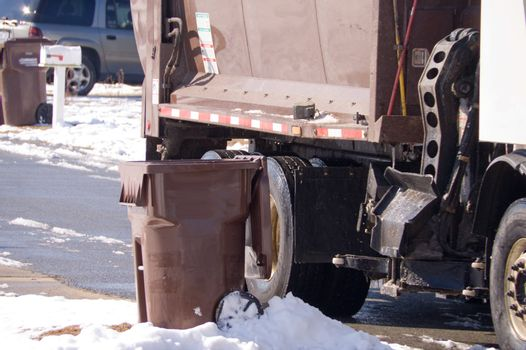 A garbage truck getting ready to pick up a garbage can.