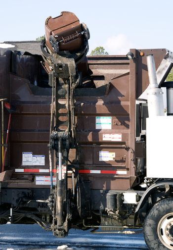 A gabage truck automatically emptying a garbage can.