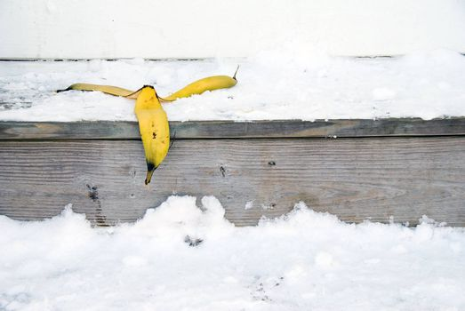 A banana peel on snow covered steps.