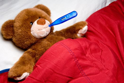 A sick teddy bear with a thermometer in his mouth.
