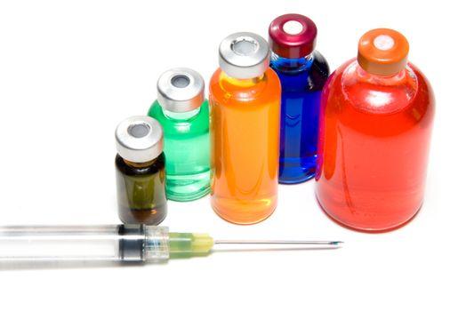 Several prescription medicine vials and a syringe.