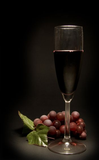 A glass of red wine and a bunch of grapes.
