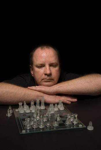 A man involved in a competitive chess match.