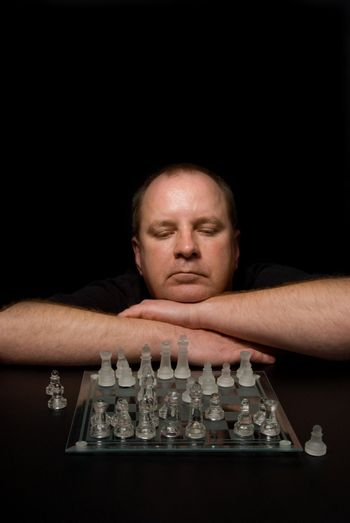 A man involved in a competative chess match.