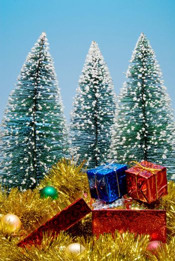 Christmas trees covered in snow surrounded by presents.