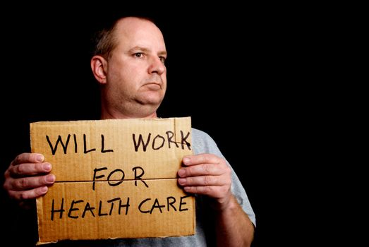 A man holding a sign that implies that he will work for healthcare.