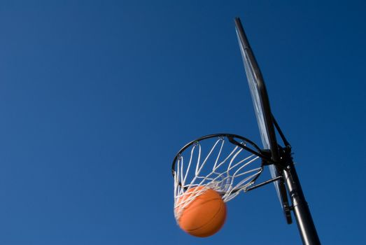 A basketball and goal waiting for a game to start.