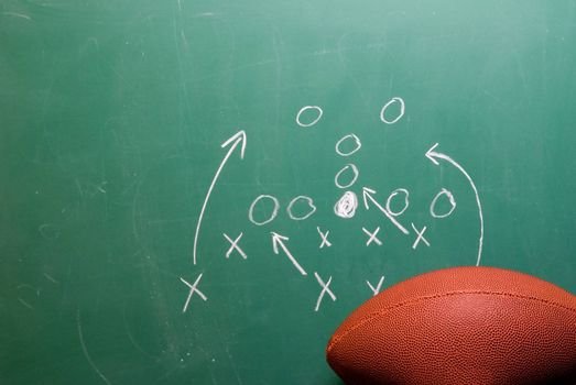 A coaches football play on a chalkboard.