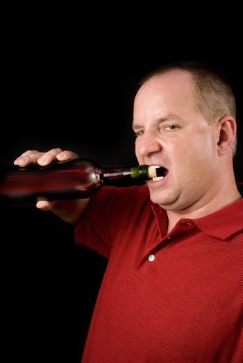 A wine connoisseur uncorking a bottle of red wine