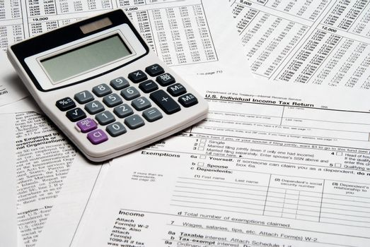 A calculator sitting on top of tax forms.