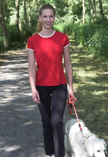 Pretty blond woman walking in the woods with her dog