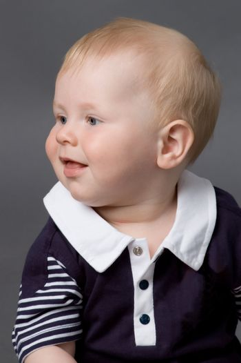 The small smiling child in studio, on a grey background