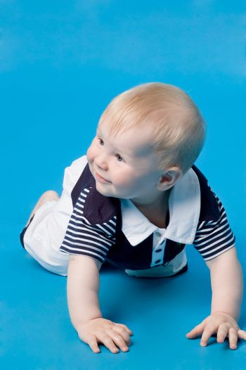 The small smiling child in studio, on a blue background