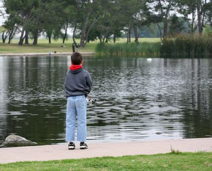 Young fisherman enjoying the sport of fishing in a lake or pond