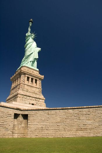 statue of liberty, clear blue sky, no people in picture