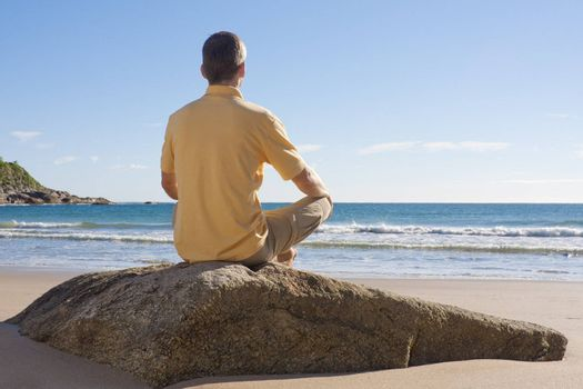 Man sitting on a rock at the beach and meditating