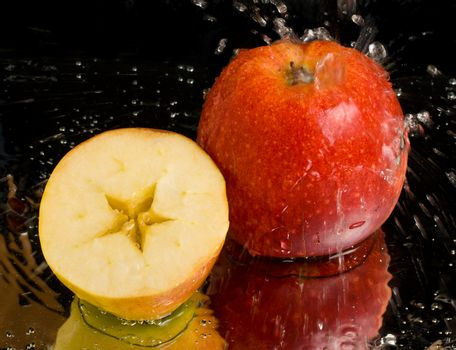full apple and half with water splashing on black