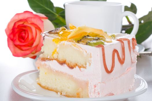 piece of cake with fruits rose and cup, isolated on white
