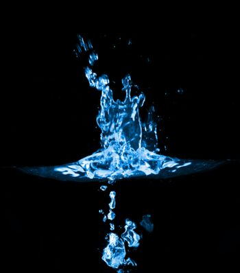 close-up splash in blue water, isolated on black