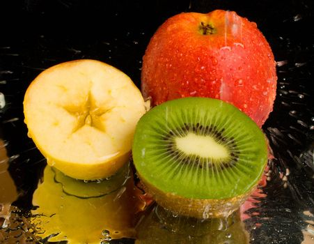 water spray on kiwi and apples, on black