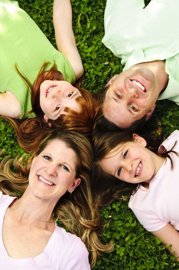 Portrait of happy family laying  on grass looking up heads together