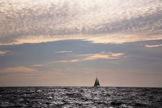 Lone sailboat on horizon