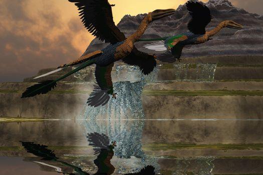 Two Microraptor dinosaurs fly near mountain waterfalls in prehistoric times.