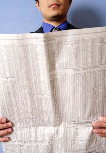 A businessman reading a financial newspaper