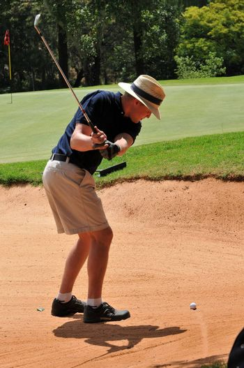young sporting adult man playing golf shot out of the sand bunker hazard onto the green with the ball visible